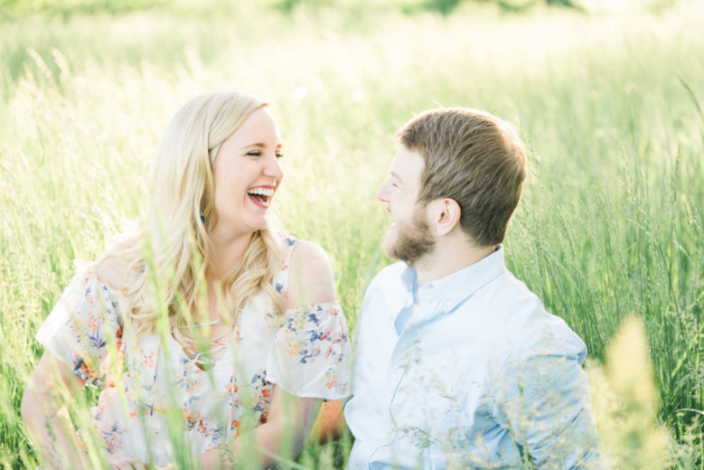couple laughs at each other in a pasture in Texas for a photographer