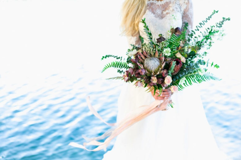 wedding floral idea of a boho bridal bouquet with a king protea by the Pacific Ocean