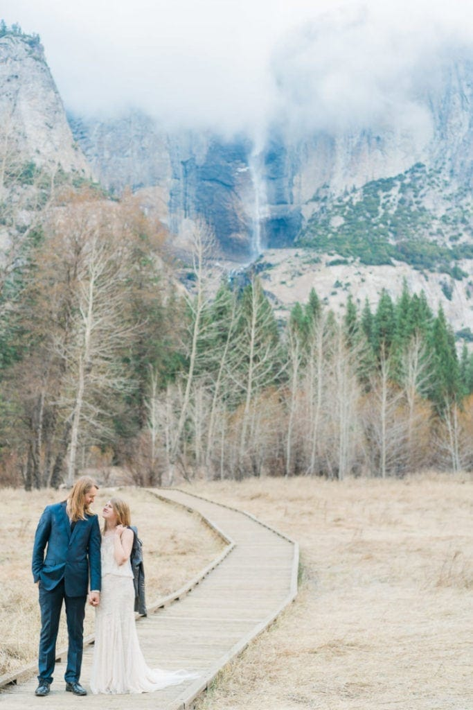 couple on a hiking trail in Yosemite with Yosemite Falls in the background