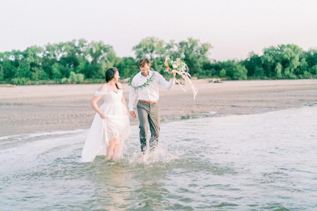 fun couple at their adventure elopement on a river sand bar