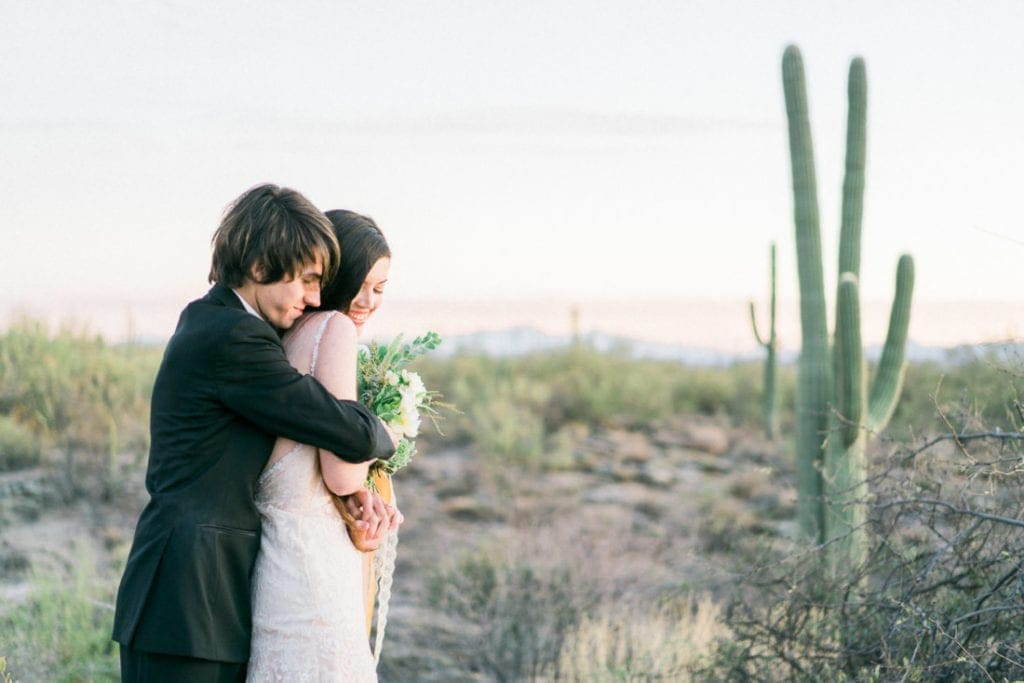 couple cuddles in the desert at their adventure wedding