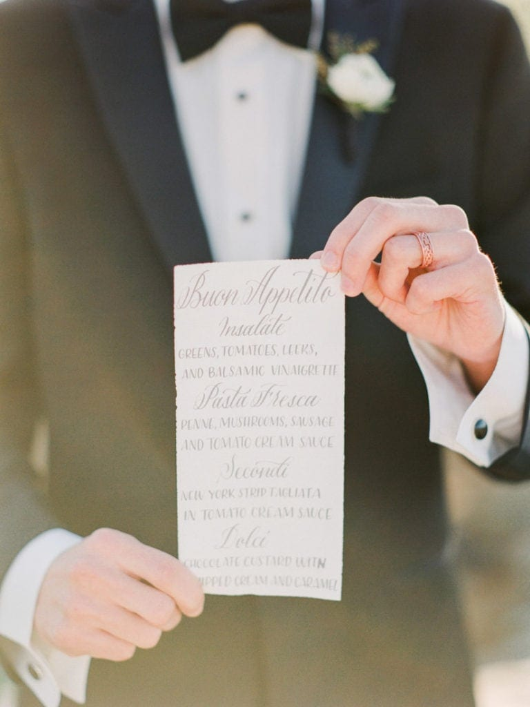 groom holding a menu for a black tie luxury wedding