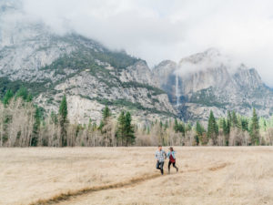 couple running through the valley on an adventure session in Yosemite