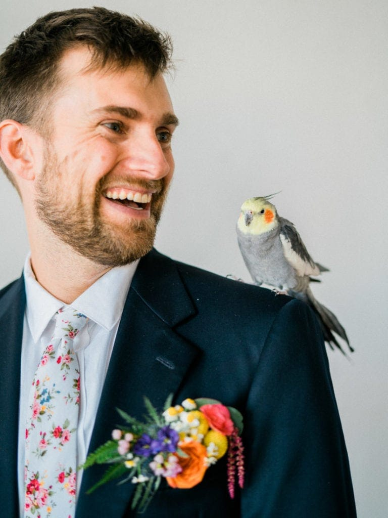 groom with a parrot on his shoulder