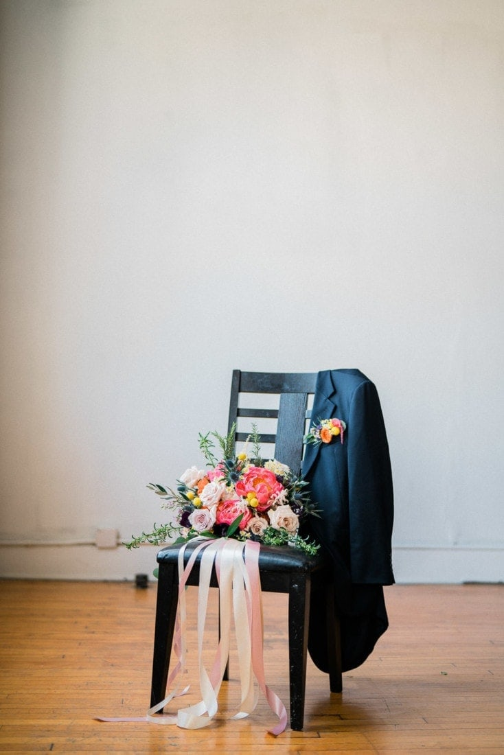 floral pocket square on a groom's suite and a bride's colorful spring bouquet
