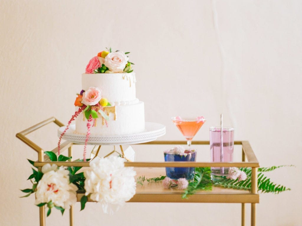 cake table setup on a vintage gold cart with peonies