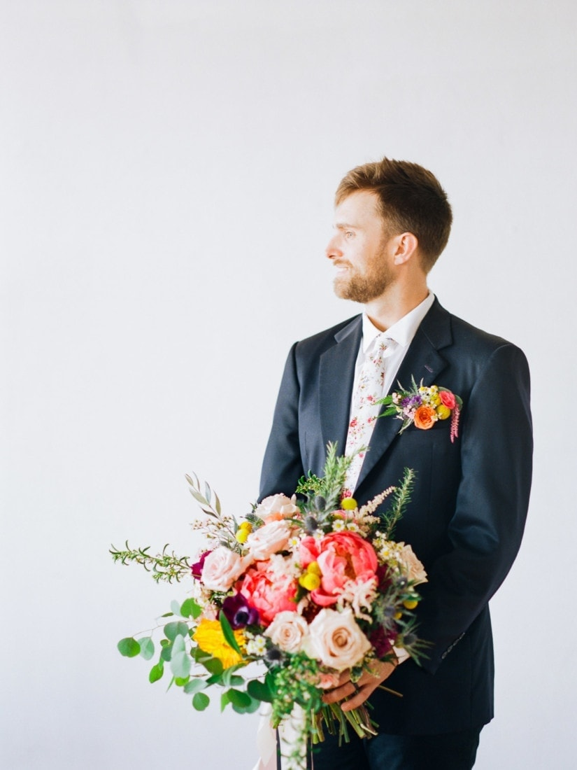 groom holing bouquet with a floral pocket square | wedding floral ideas