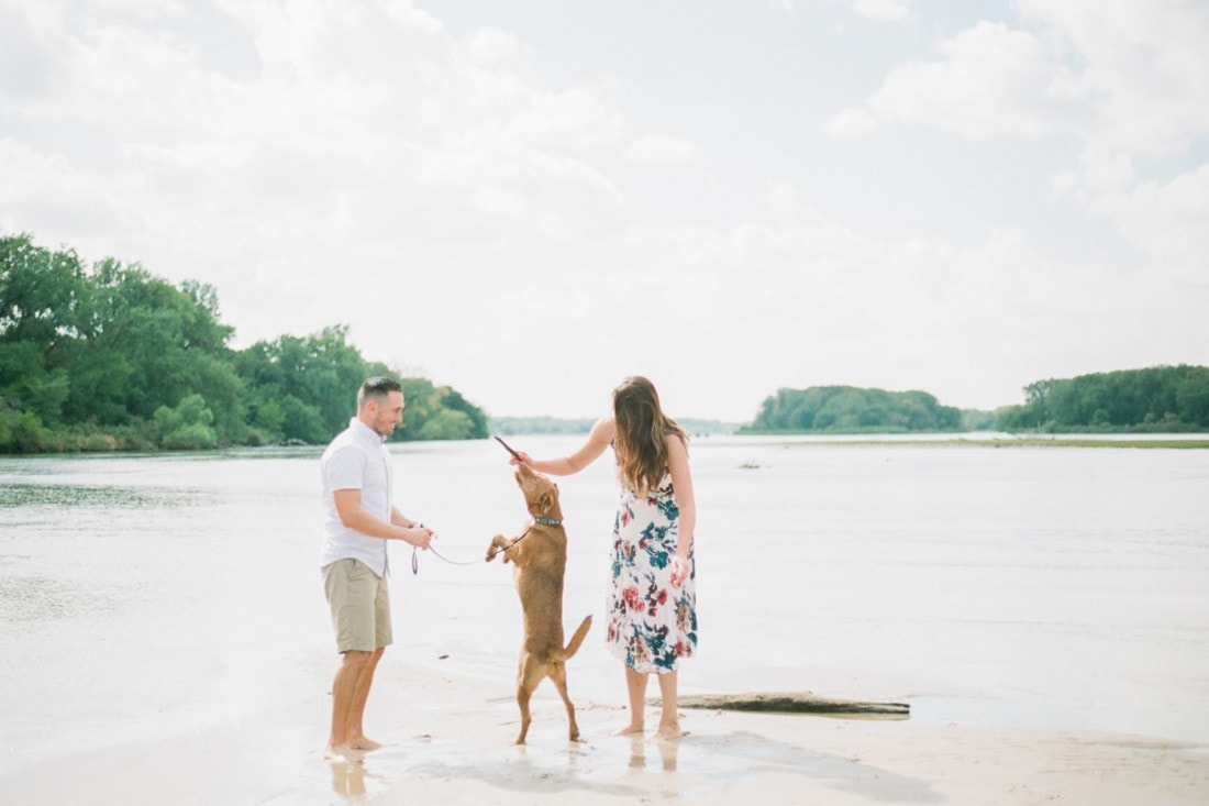 couple playing on the river with their dog on a family session in Nebraska