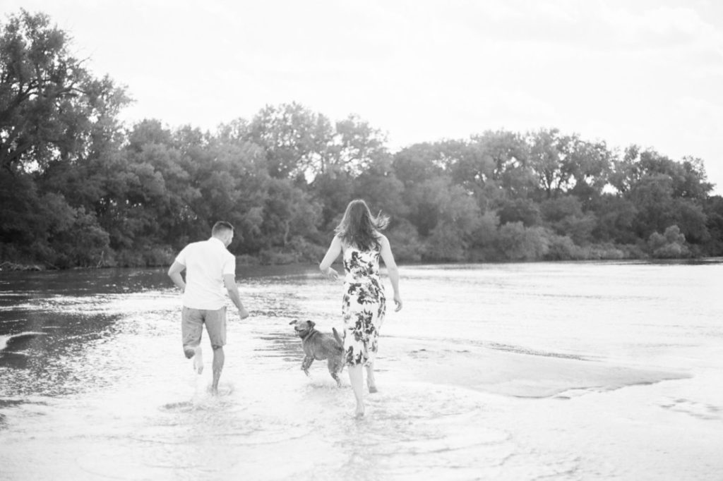 couple running on the Platte River playing with their puppy