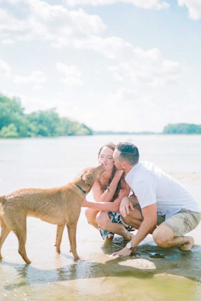 couple kissing and getting kisses from their dog