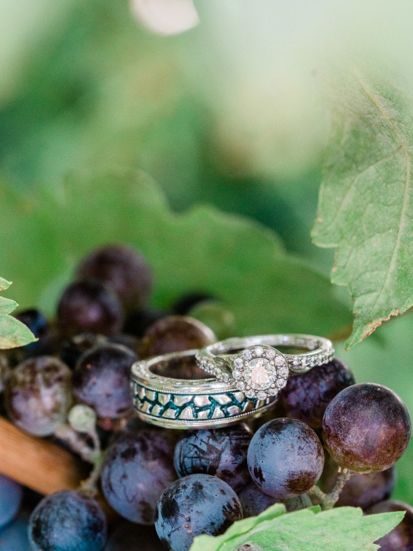 custom wedding bands | wedding ring shot on grapes in a vineyard in Palisade, CO