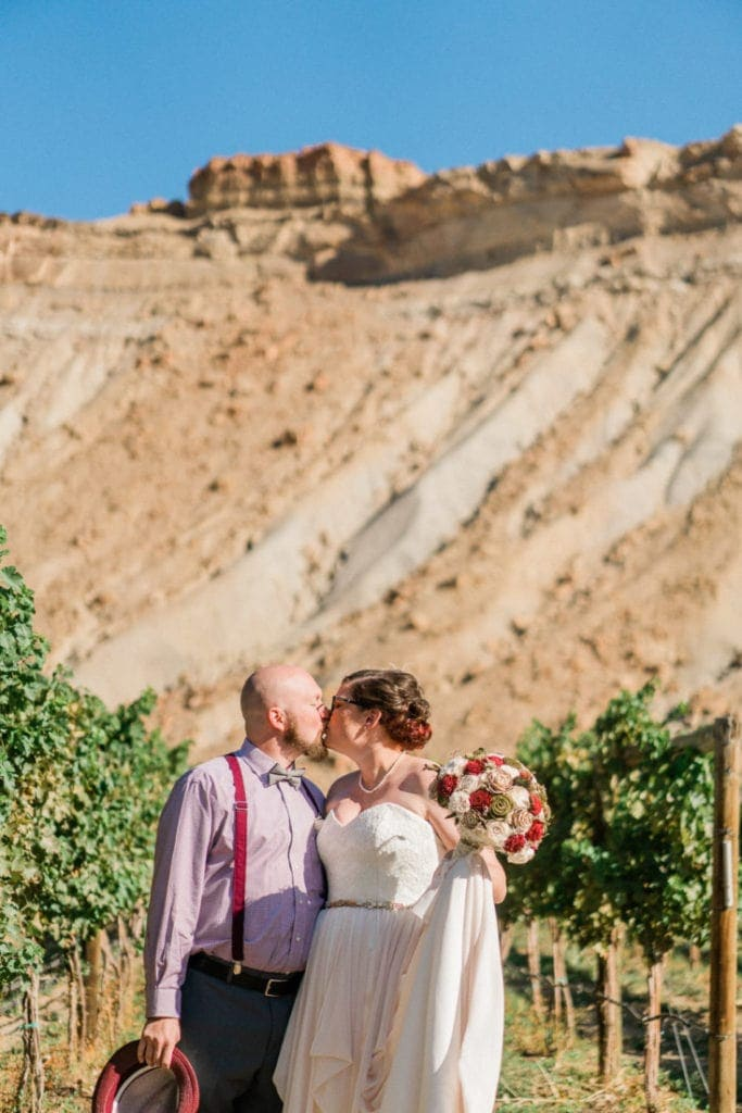 couple gets married under the bluff in the vineyards of Palisade