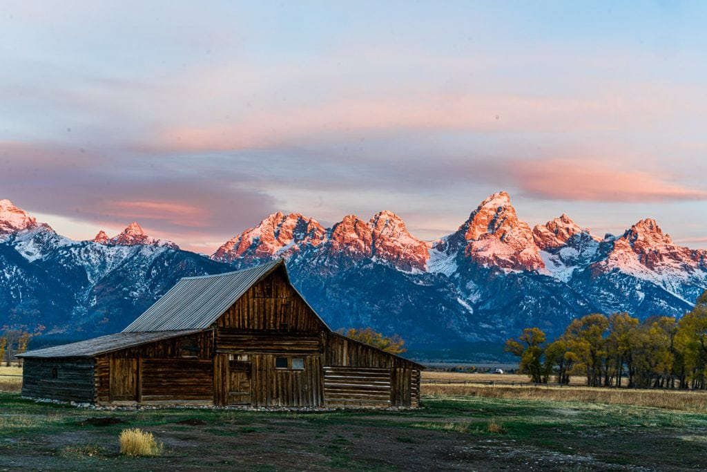 sunrise at a barn with the Grand Tetons in the background