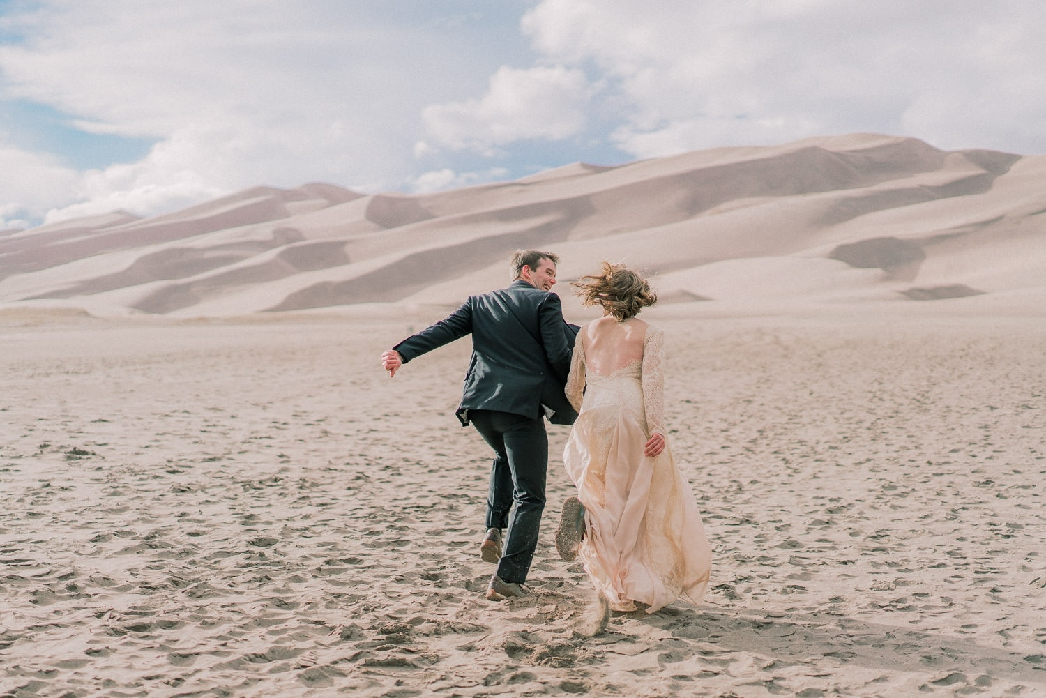 bride and groom runs towards the Great Sand Dunes of Colorado