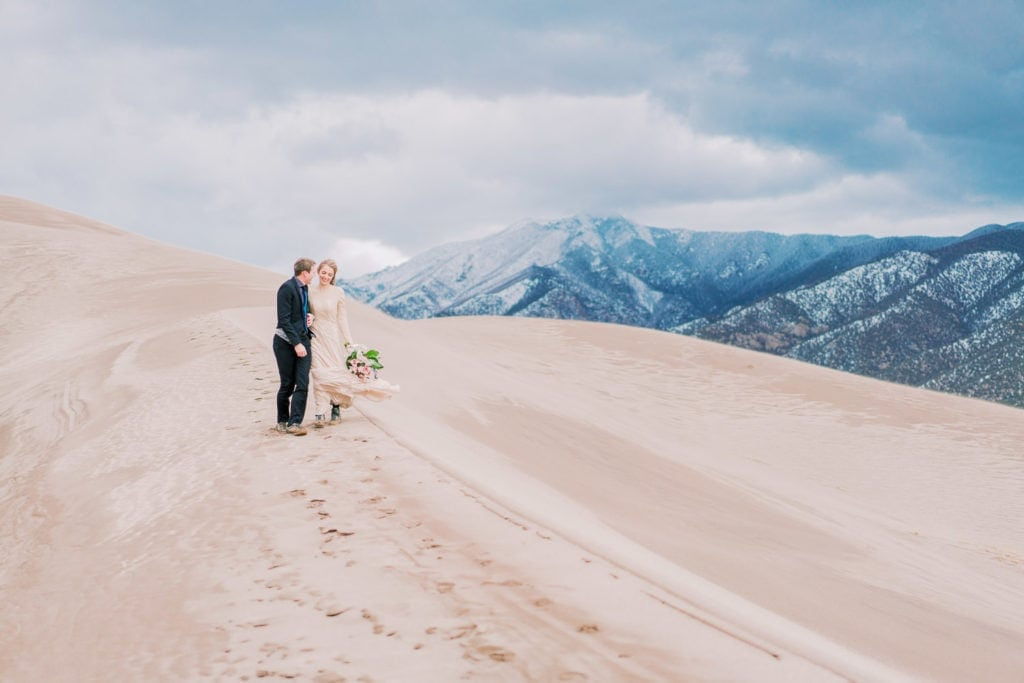 couple walks along the ridge of a sand dune in Colorado