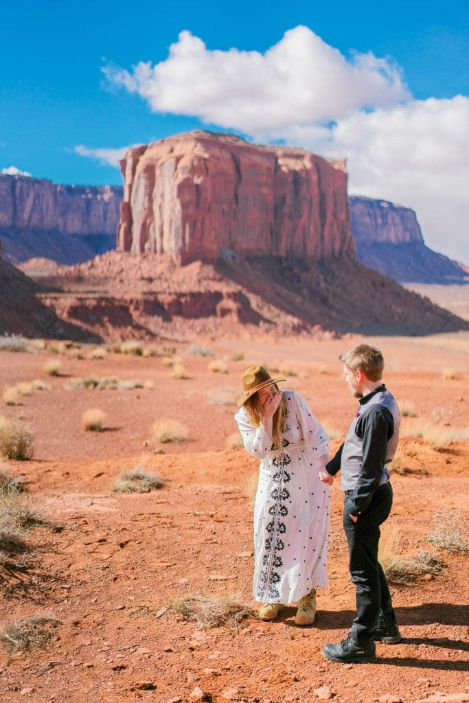 couple laughs at an engagement session in Monument Valley