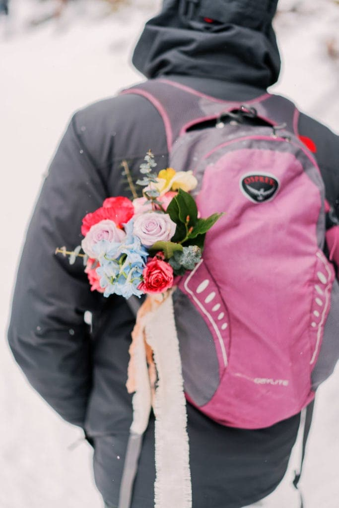 bouquet in an Osprey backpack during a winter hiking elopement in Rocky Mountain National Park in Colorado near Estes Park | Estes Park wedding photographer | Rocky Mountain National Park wedding photographer