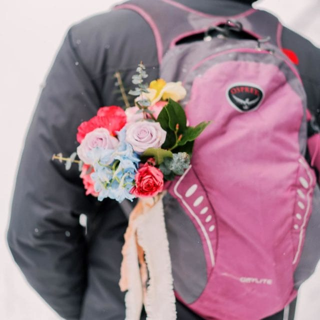 bouquet in a backpack during a winter elopement in Colorado