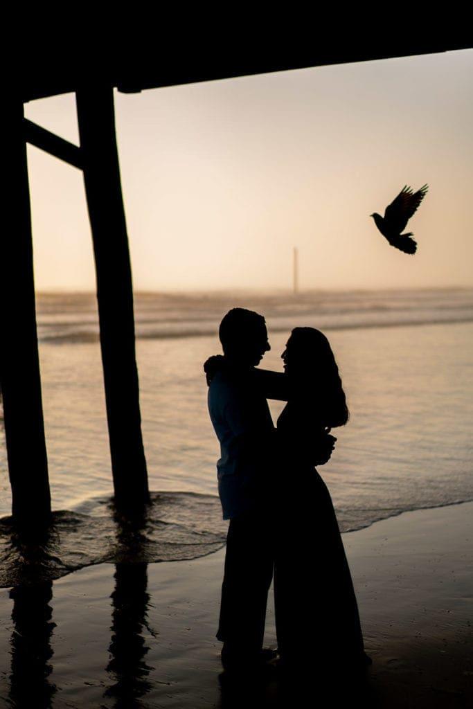 elopement under an ocean pier at sunrise on a beach in Florida