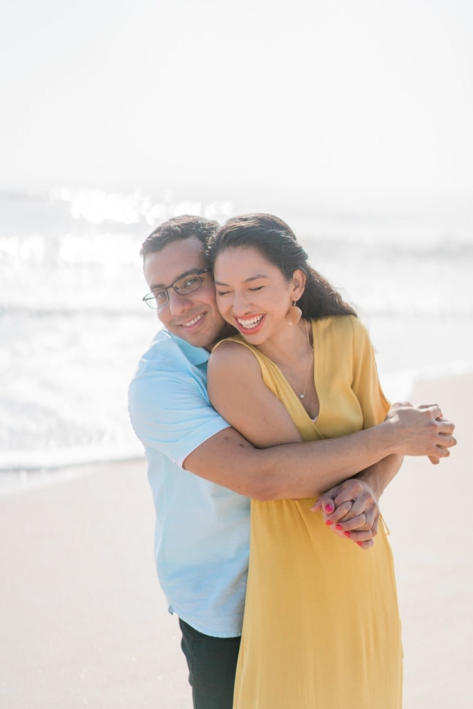 couple embraces each other during a Florida engagement session at the beach