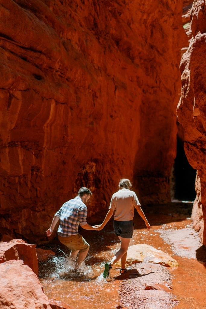 fun engagement photography in Moab, Utah in a canyon with a creek