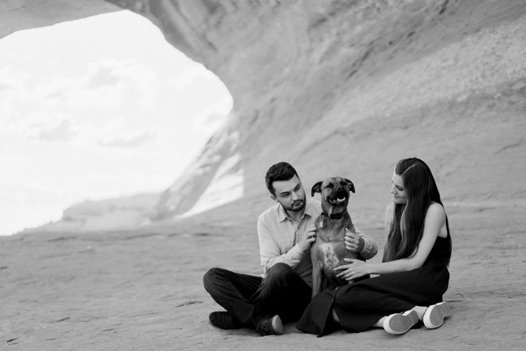 black and white photography of a couple and their dog under an arch