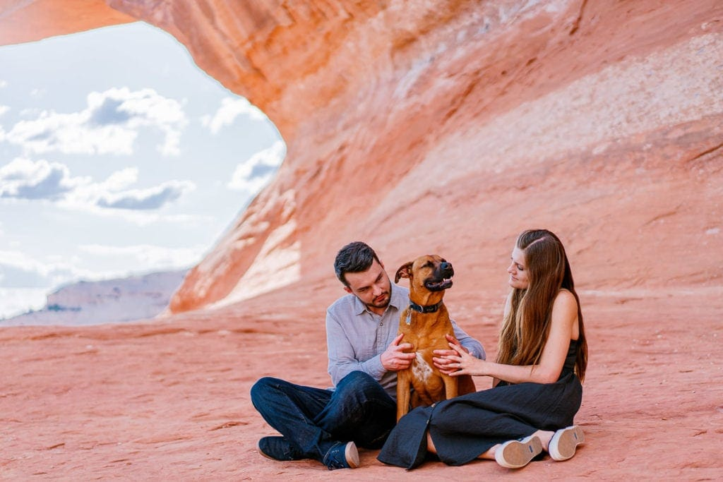 couple and their dog during an engagement session under an arch in Moab