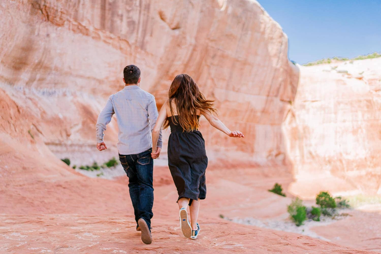 running during a fun engagement session in Moab
