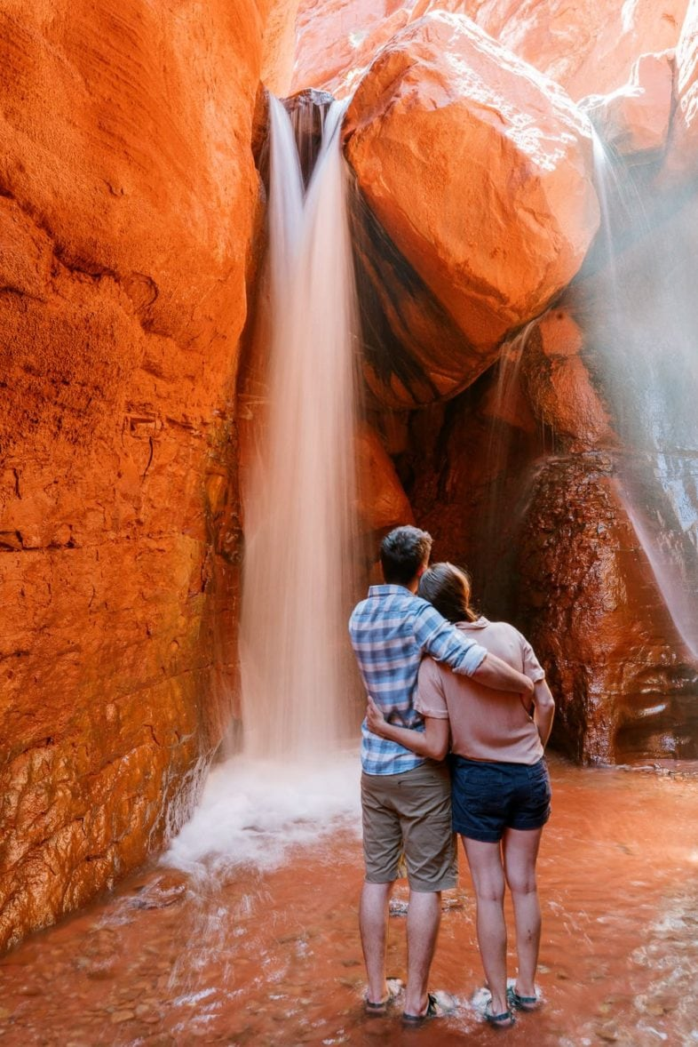 engagement photos at a waterfall in a canyon in Moab, Utah