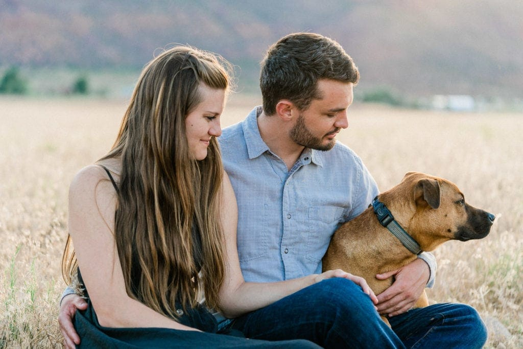 engagement session in Moab, Utah with a couple and their dog at sunset