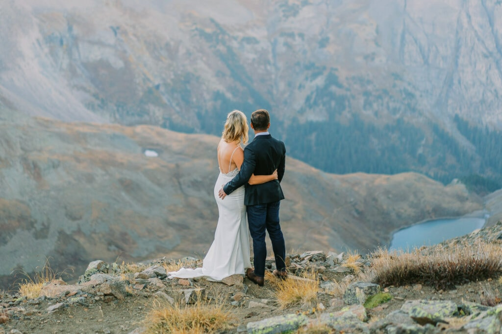 A couple who eloped in Glacier National Park overlooks a lake at sunrise.