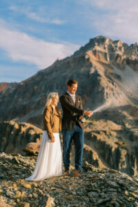 Bride and groom pop a bottle of champagne on top of a mountain after their elopement in Glacier National Park at sunrise.