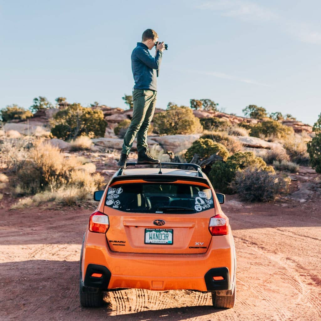 Malachi Lewis at Shell Creek Photography in Moab, Utah on top of his orange Subaru