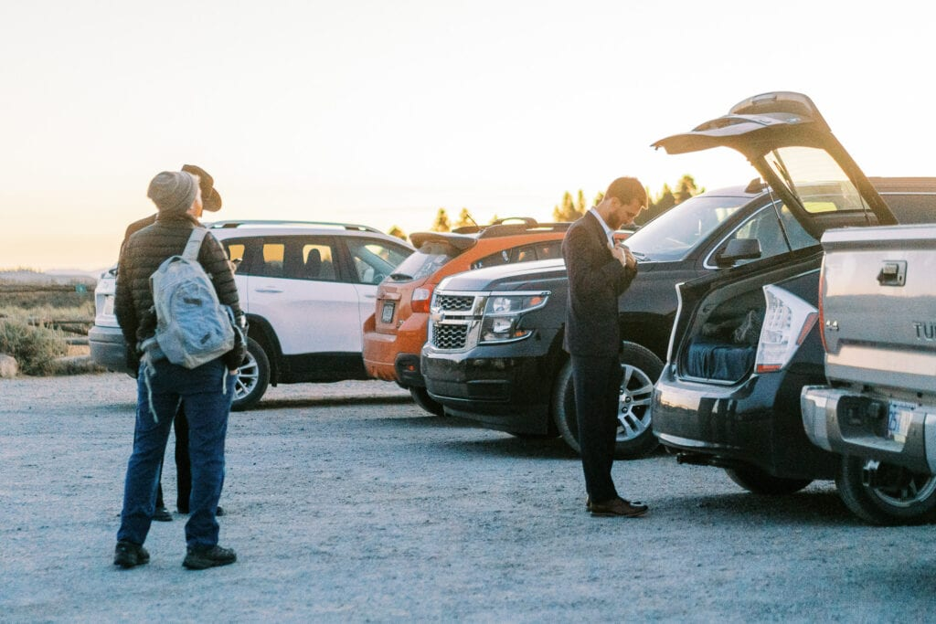 Groom gets ready in the back of his car at sunrise for his elopement in the Tetons.