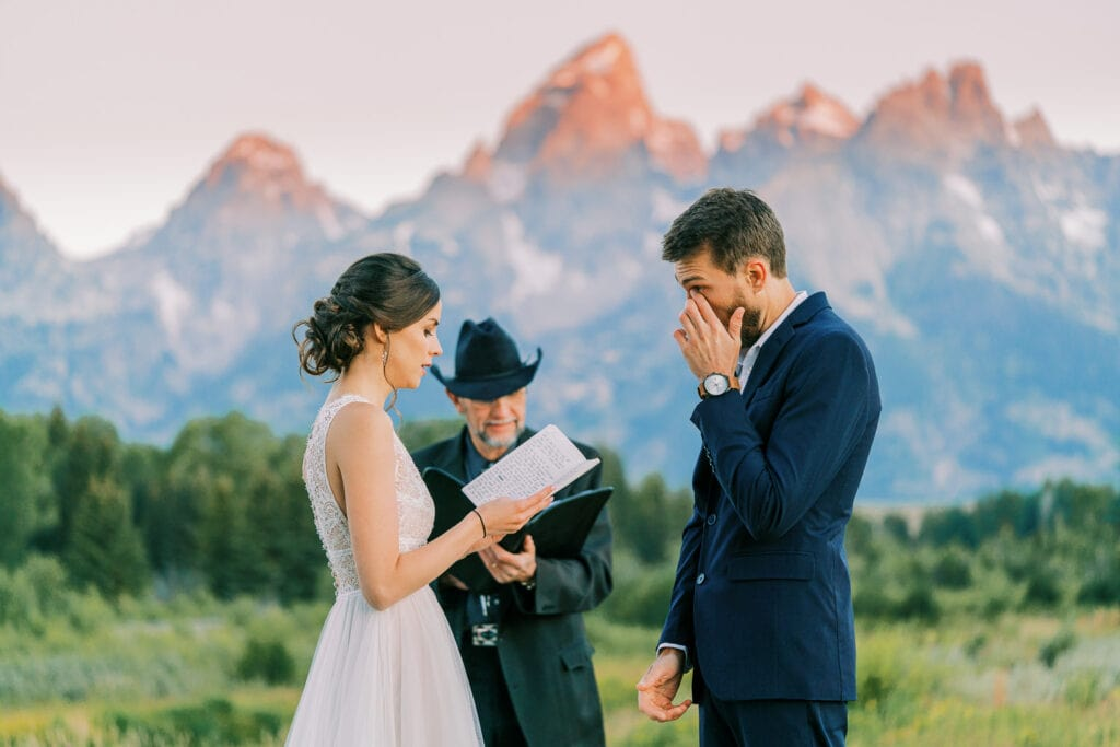 Groom wipes away tears at a wedding ceremony in Wyoming at sunrise.