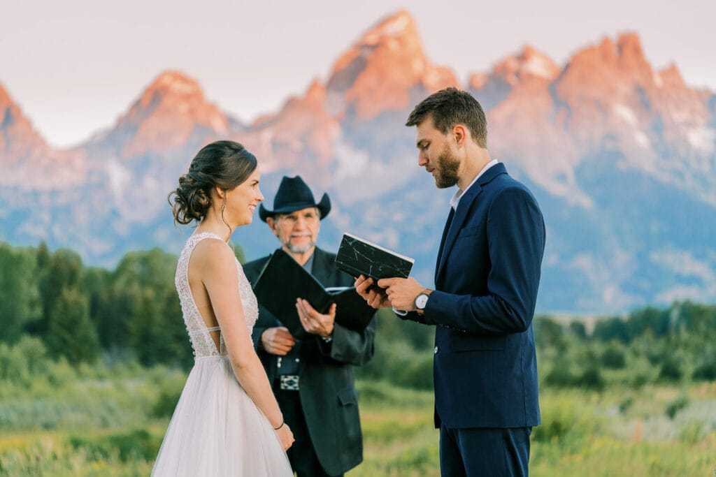 Groom reads his vows to his bride at sunrise in front of the Grand Teton Mountains in Wyoming.