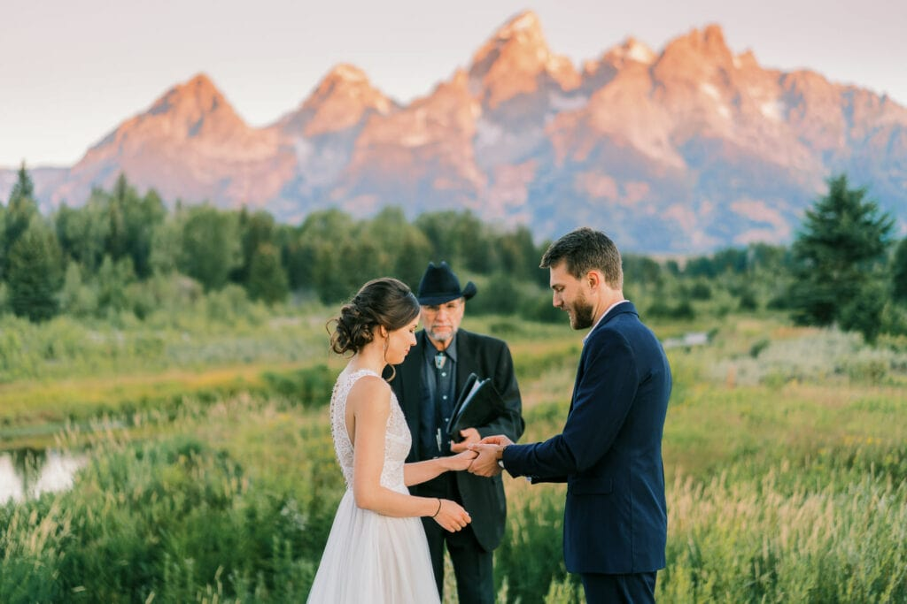 Groom puts a ring on the brides hand during their sunrise elopement ceremony.