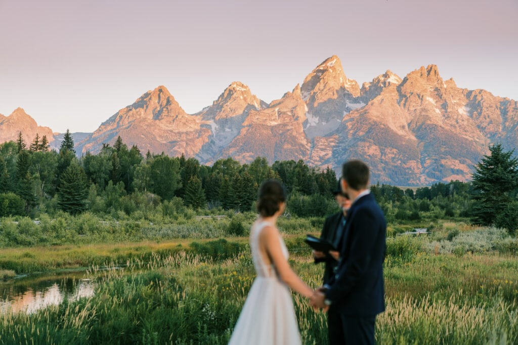 Bride and groom have a sunrise ceremony in Grand Teton National Park with focus on the mountains.
