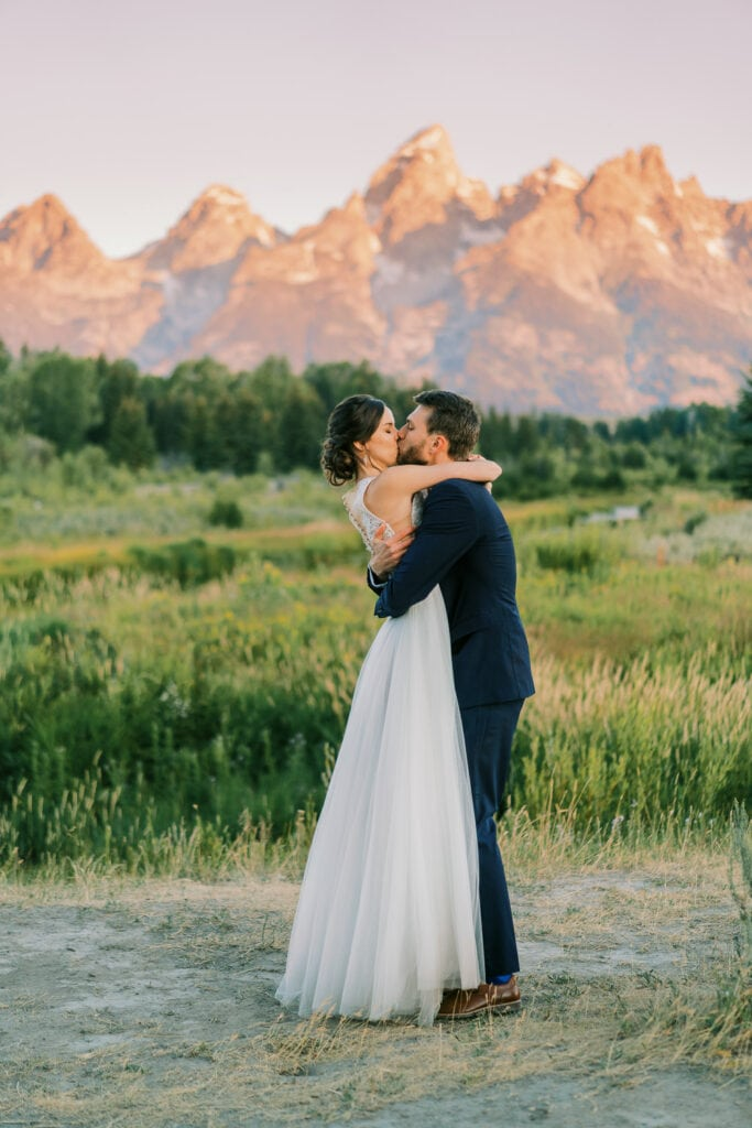 Bride and groom go in for a first kiss at their elopement at sunrise in Grand Teton National Park.