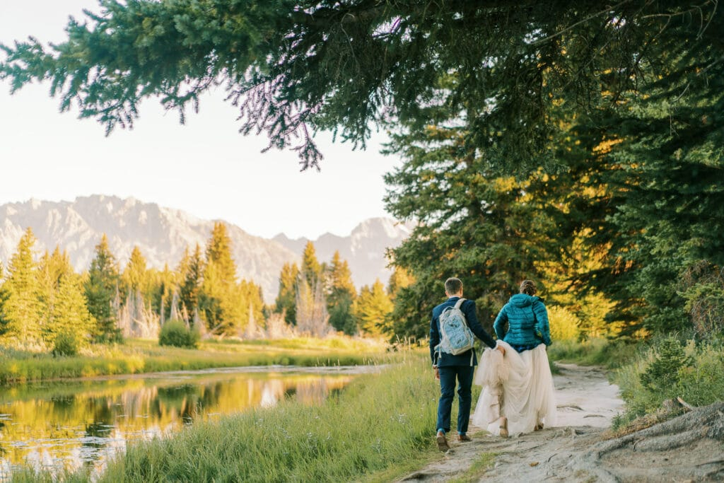 Groom hold his bride's dress for hiking at their elopement in Grand Teton National Park.
