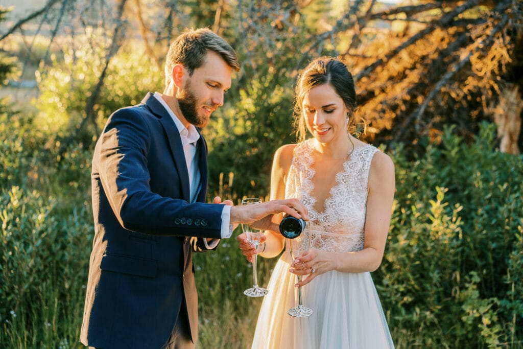 Couple pours champagne for a toast at their elopement.