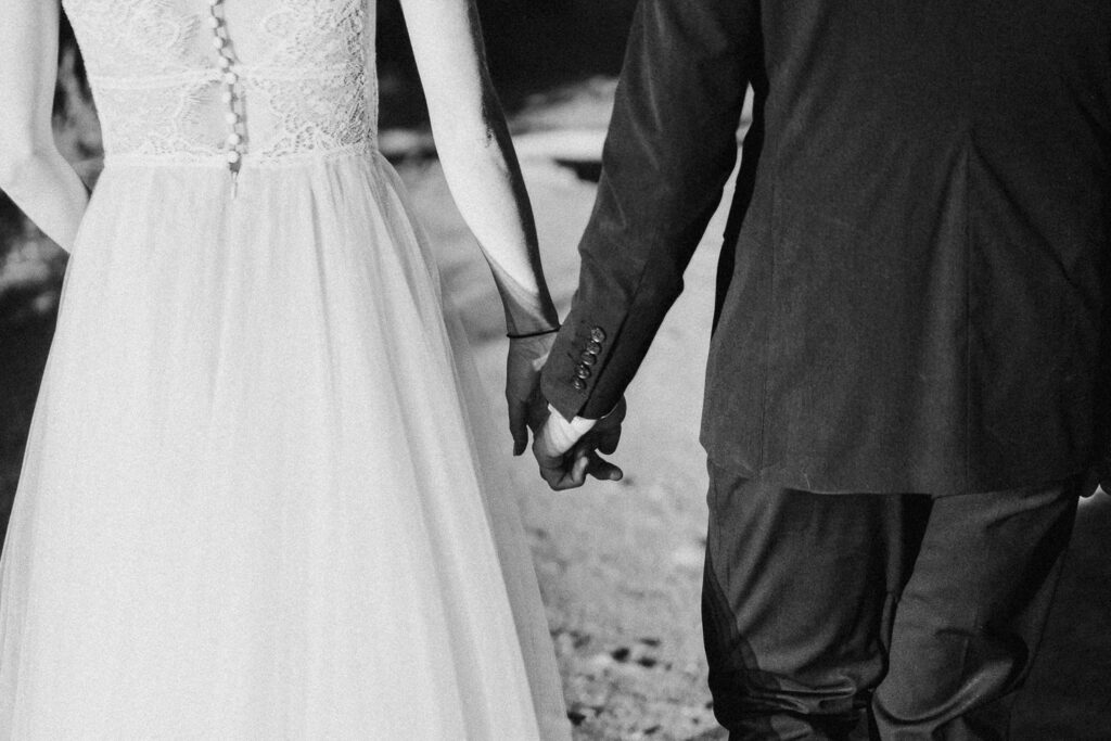 Grainy black and white romantic film photo of a bride and groom holding hands.