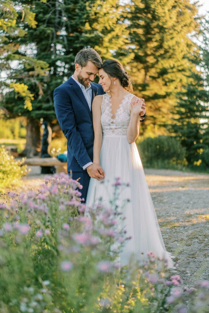Bride and groom embrace in front of some purple wildflowers during their National Park elopement.