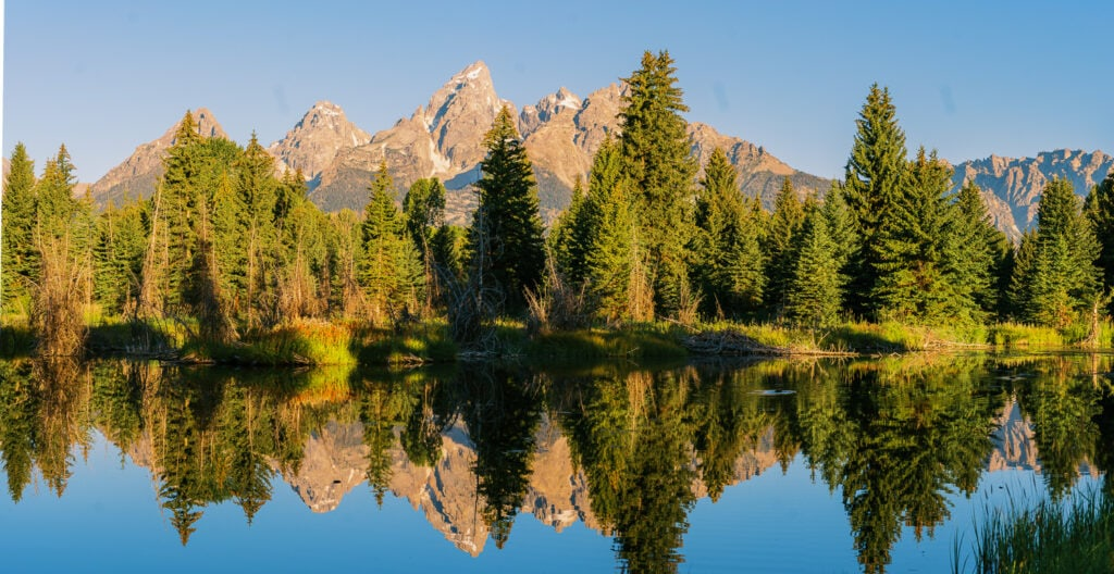 View of the Grand Teton mountains from Schwabacher Landing after sunrise with a reflection in the beaver ponds.