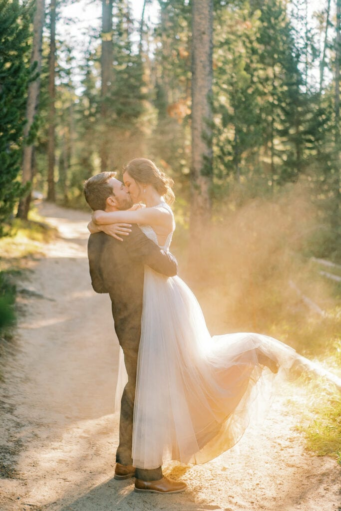 Groom lifts up bride for a passionate kiss on a dusty trail when hiking for their elopement.