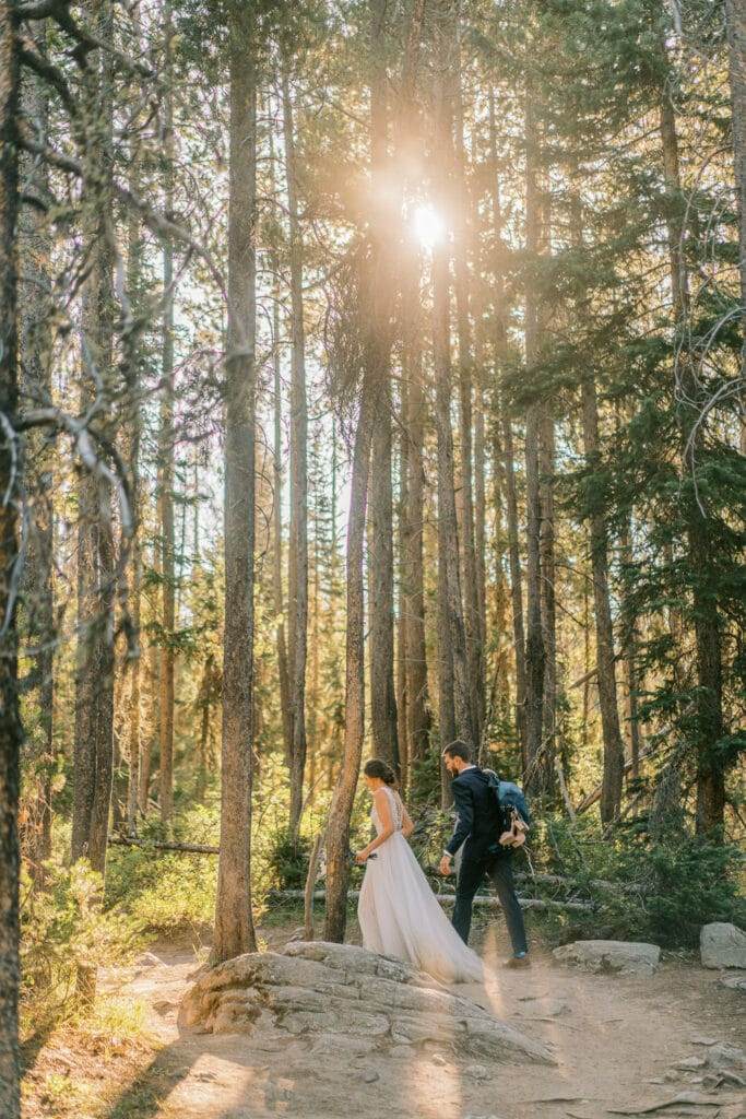 Bride and groom hiking along in a forest with the sun coming through the trees just after sunrise.