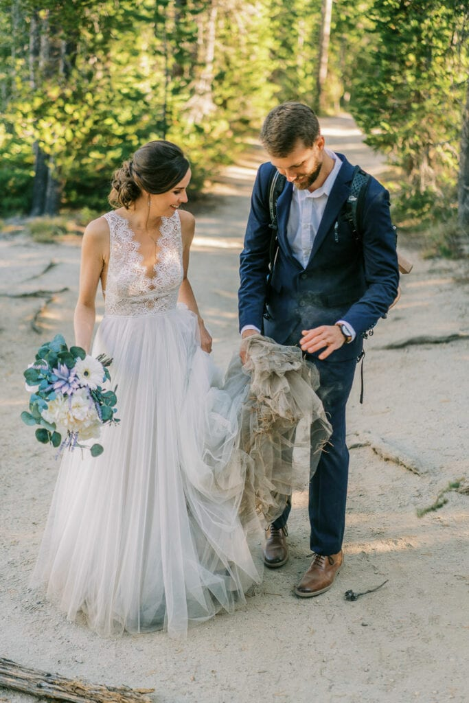 A bride has a very dirty dress and the groom picks some sticks out of it when hiking on their elopement day.