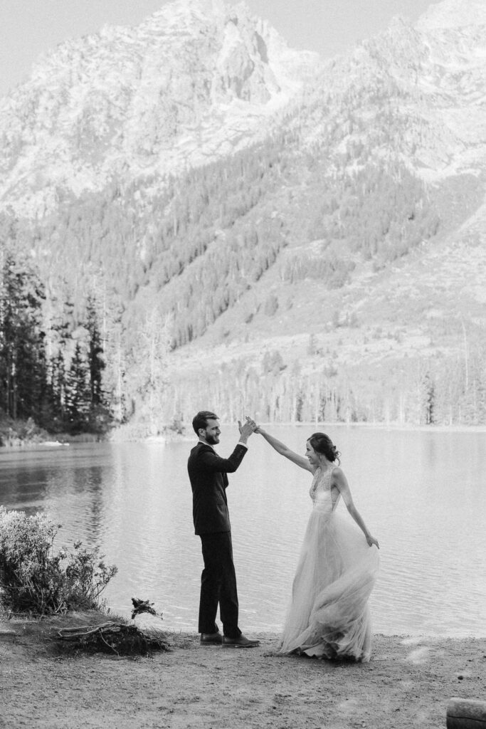 Black and white photo of a bride and groom having a first dance on the shores of a lake in Grand Teton National Park.