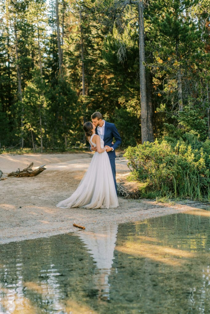Bride and groom kiss on the shores of a lake in Grand Teton National Park.