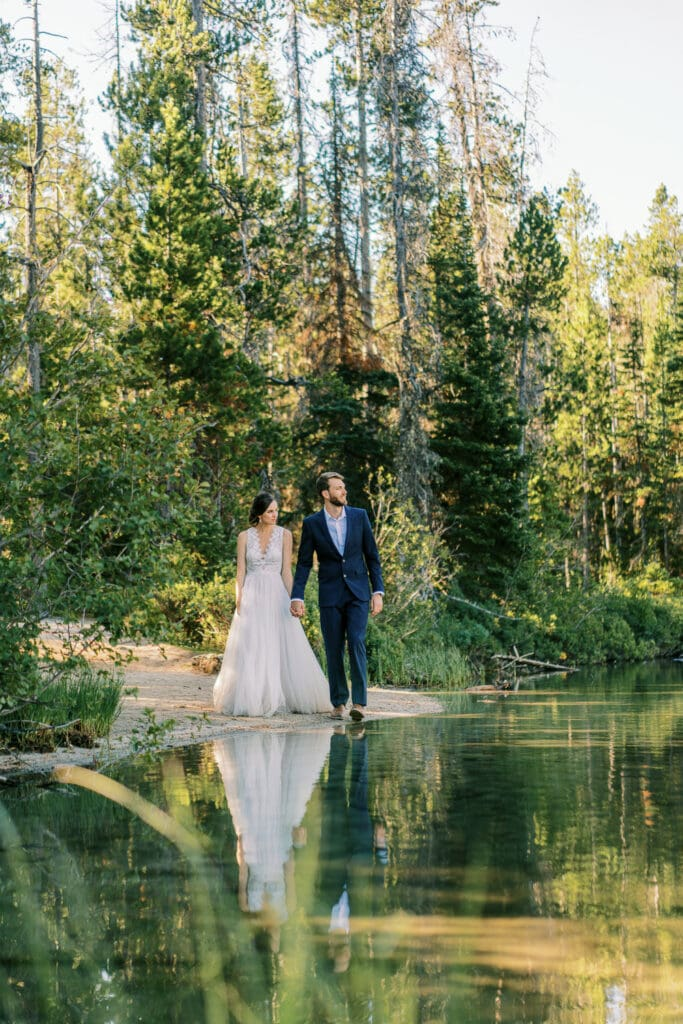 Bride and groom walk along the shores of a lake during their Grand Teton elopement.